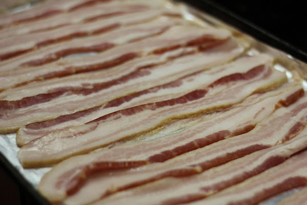 Lay bacon flat on a foil lined baking sheet. Make sure to use a...
