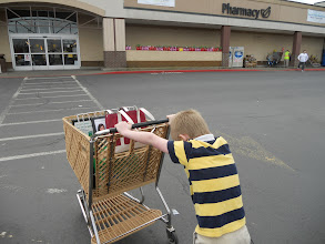 Photo: Nathan loves to push the cart. As long as Mommy gets to leave her bag with coupons in the cart , it is usually ok.