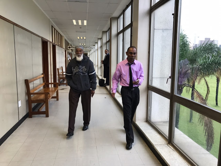 Mohammed Ebrahim, right, and his father Sheik Ebrahim Shah in the halls of the Durban magistrate's court. Ebrahim has been formally charged with the murder of Miguel Louw.