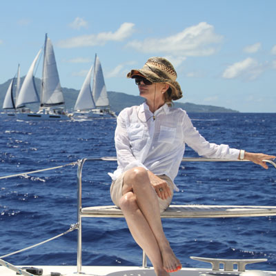 woman relaxing on catamaran with boats in the distance