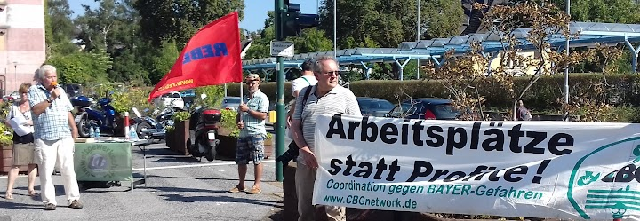 Protestler vor dem Bayer-Tor. Plakat: «Arbeitsplätze statt Profite!».