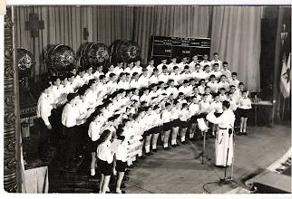 """Photo: Es un sorteo de la Lotería Nacional en el Teatro Emperador de León el día 5 de junio de 1965. """"Comenzó el sorteo con la actuación de la laureada Escolanía de los PP. Dominicos de la Virgen del Camino, que interpretó """"El Romeral"""", a cinco voces, de E. Ramírez; """"La cinta del pelo"""", canción leonesa, de J. Hernández y el """"Digno es el Cordero, de Haendel. Tanto la Escolanía como su Director, el reverendo P. Ángel Torrellas, fueron entusiásticamente aplaudidos.(  Diario de León, del día 7-6-1965)"""". Froilán Cortés está delante del P. Torrellas. Carlos Fdez.Martínez en la segunda fila (contando por la izquierda el sexto, el que tiene un triángulo blanco en la cabeza (de una partitura)"""
