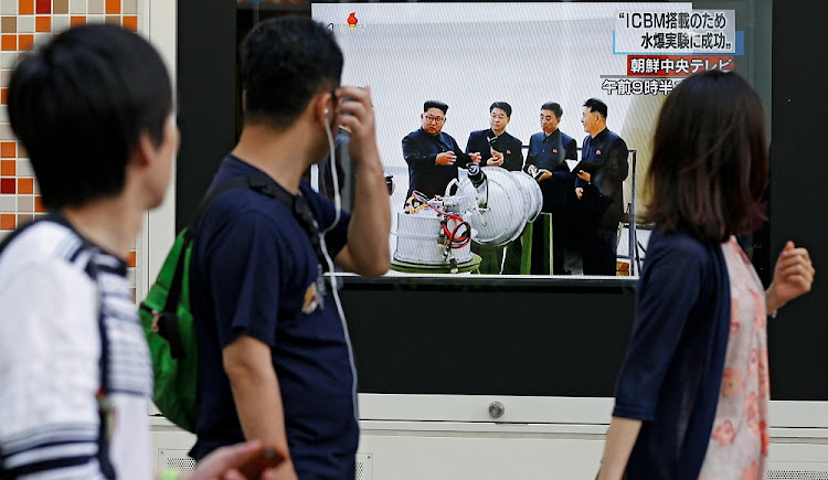 People walk past a street monitor showing North Korea's leader Kim Jong-un in a news report about North Korea's nuclear test, in Tokyo, Japan, on Sunday. Picture: REUTERS