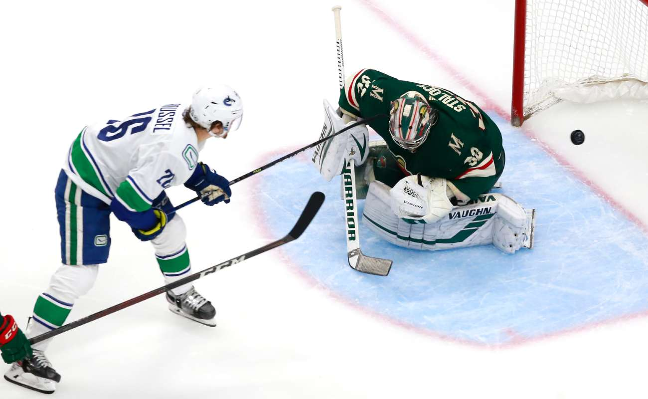 Antoine Roussel of the Vancouver Canucks scores a goal as Alex Stalock of the Minnesota Wild