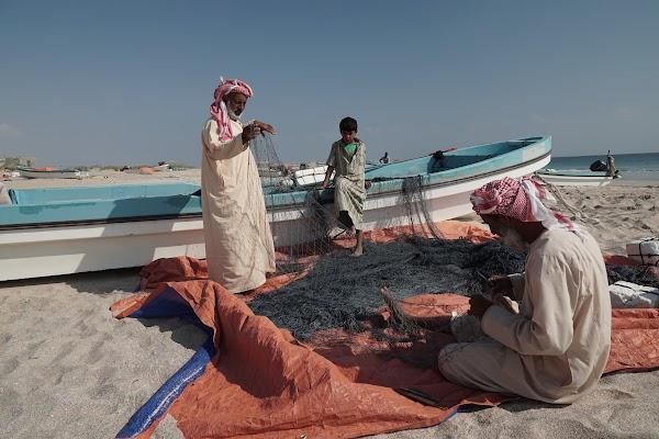 Am Strand flicken zwei Fischer ihre Netze