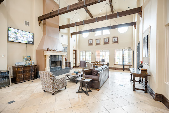 Clubhouse lounge area with high ceilings with wood beams, tile flooring, couch, chairs, fireplace, and mounted TV