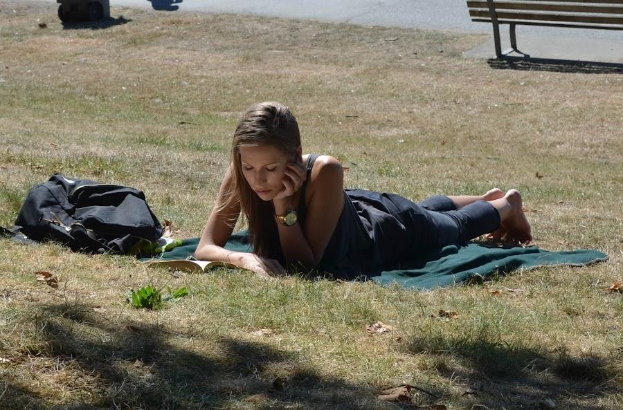 Reading at English Bay by Cory Bohnenkamp - People Street & Candids ( reading, grass, woman, book, beach, sunlight )
