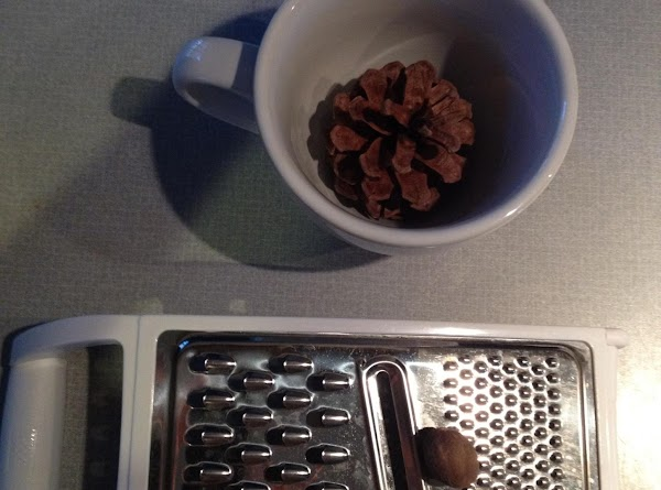 Sprinkle nutmeg over the pine cone using the cup to contain the extra. Tap...