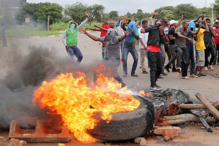 Protesters stand behind a burning barricade during protests on a road leading to Harare, Zimbabwe, January 15, 2019. REUTERS/Philimon Bulawayo/File Photo