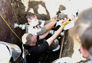 A team of emergency workers battled for four hours to rescue a baby who had been dumped in a stormwater drain.
