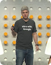 Man on stage wearing Hire with Google tee shir
