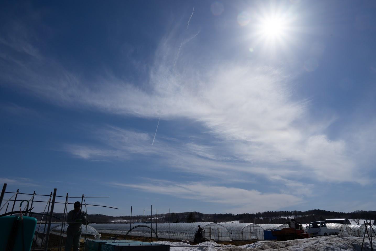 光の白線を引く飛行機雲