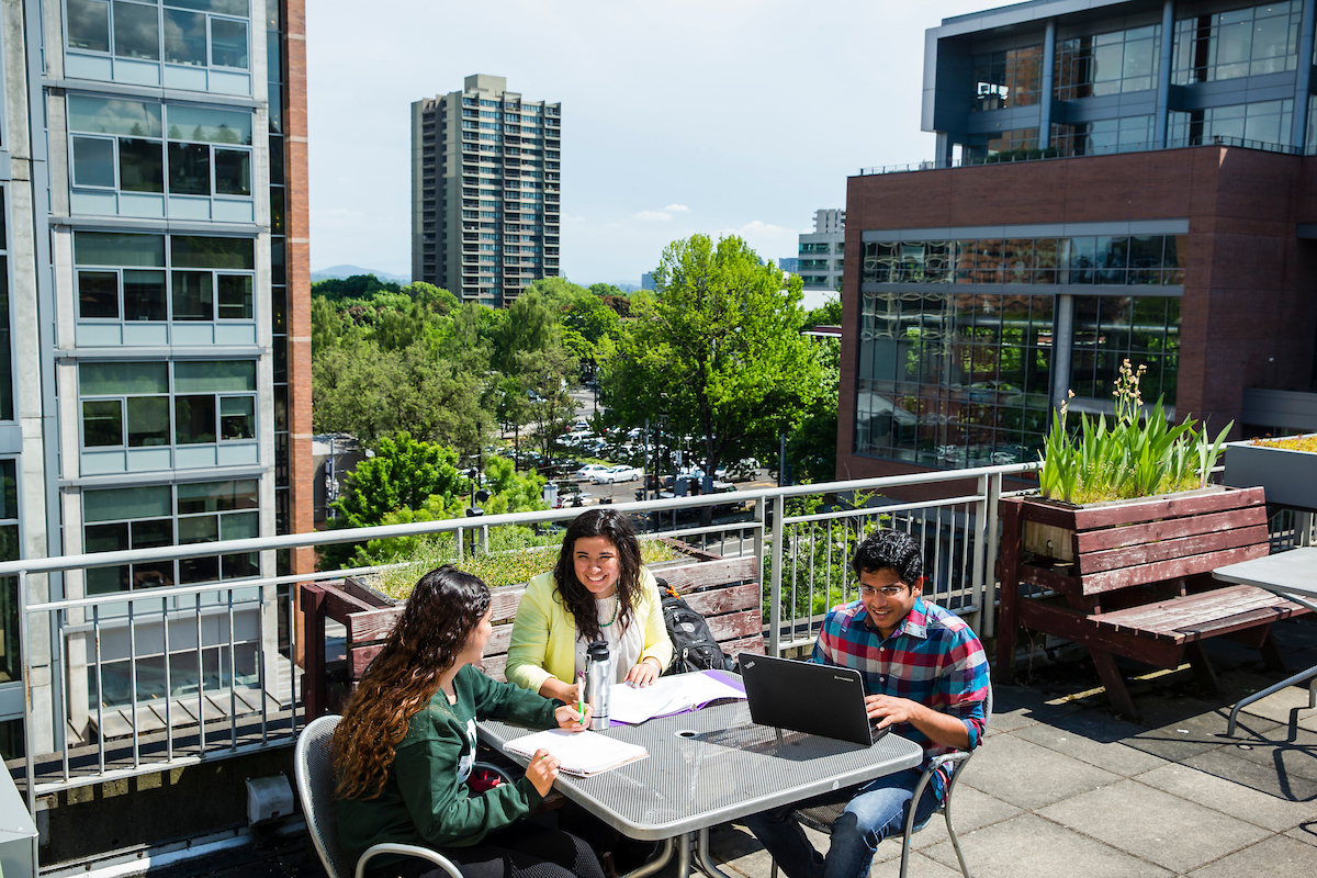 Three students chatting on a patio on campus