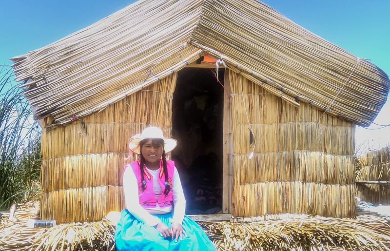 indigenous+women+sitting+hut+uros+islands+tour+puno+perù+lago+titicaca+south+america