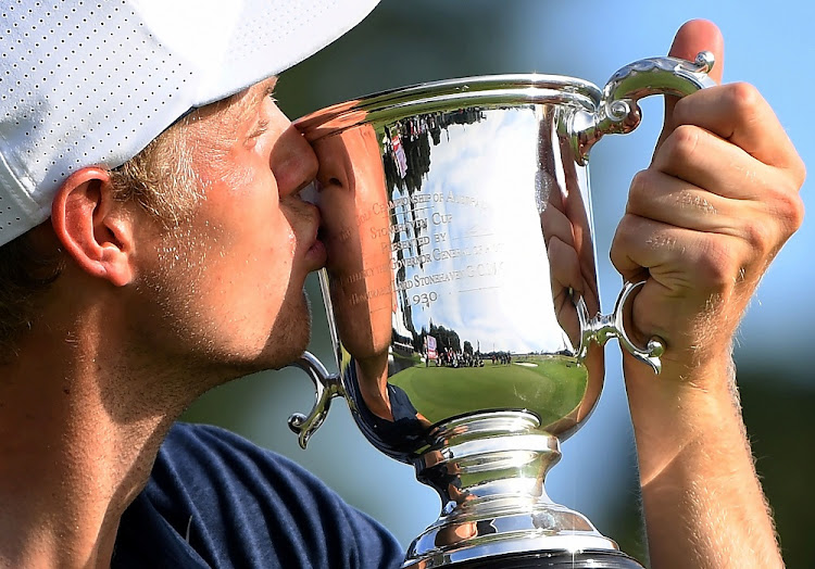 Victory from behind: Australia's Cameron Davis kisses the Stonehaven Cup after winning the Australian Open Golf Championship in Sydney on November 26, 2017. Picture: REUTERS