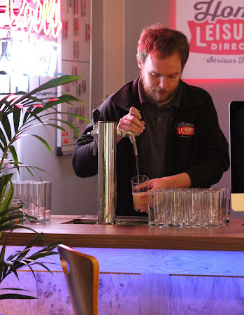 a barman pouring a beer out of a beer tap