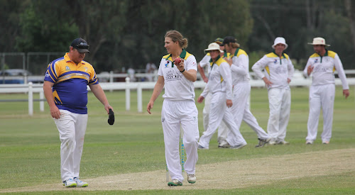 Tatts opening bowler Ryan O'Neill returns to his mark, as his teammates continue to celebrate a wicket. O'Neill has taken eight wickets in two 45-over games this season, including a five-wicket haul against Crossroads Hotel on Saturday in his side's 74-run victory.