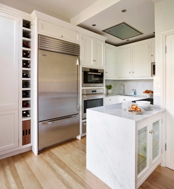 small white kitchen with shaker cabinets and marble waterfall countertop. bright colors illuminate the space, including white wall paint and light wood floors