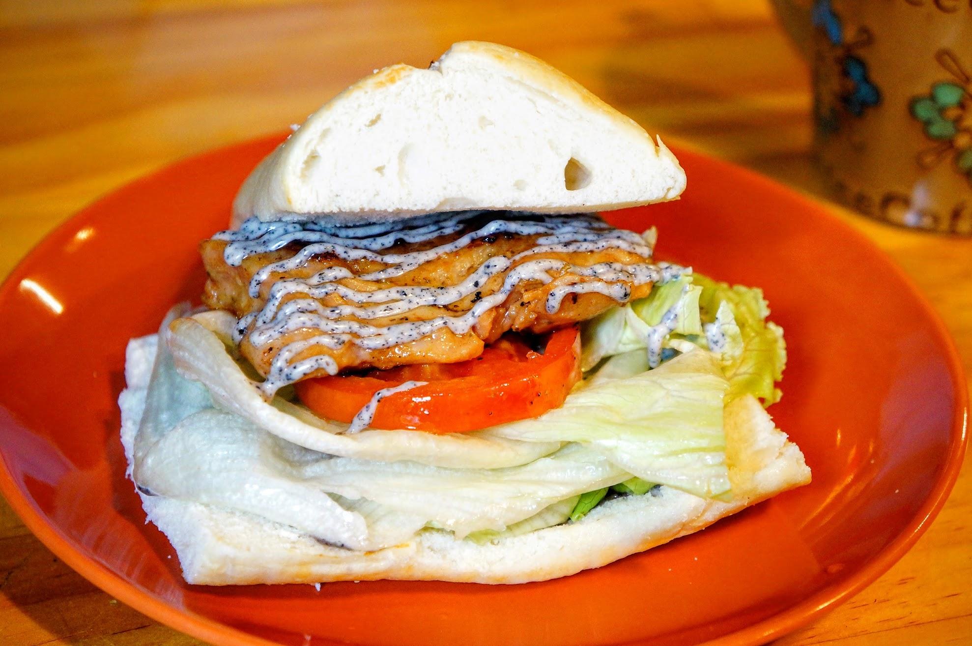地中海香嫩雞排堡,中間雞排上方有淋上芝麻沙拉醬,底下則是新鮮番茄切片和生菜