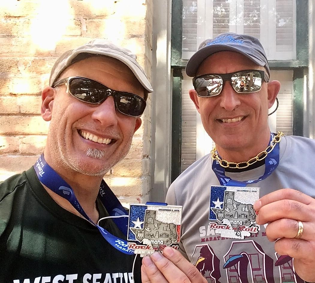 Jeff and his brother smiling with their San Antonio Rock 'n' Roll Marathon metals
