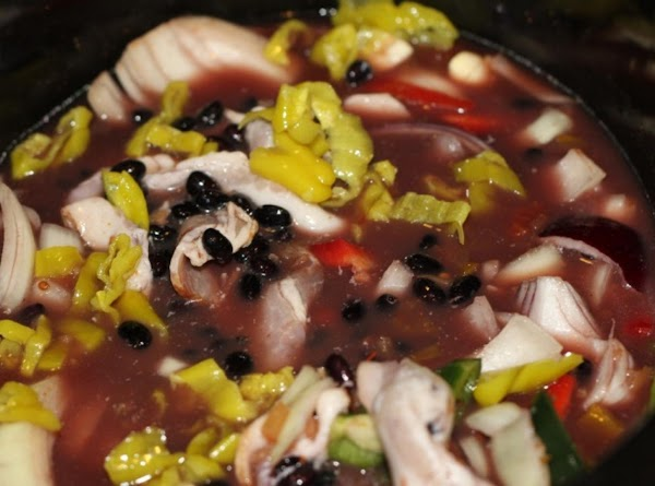 In a crock pot, add soaked beans and cover with chicken stock. I used...