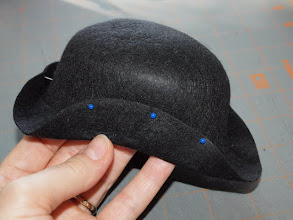 Photo: Fold up 3 sides of the brim to make a triangle shape and stick the pins through the brim and into the crown of the hat.  The pins will hold the brim in place while it dries.  You may need to spritz it with a little more water as your work.