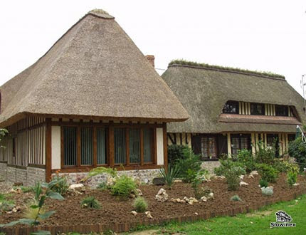 Dom z muru pruskiego z dużymi oknami i pokryciem z szarej trzciny