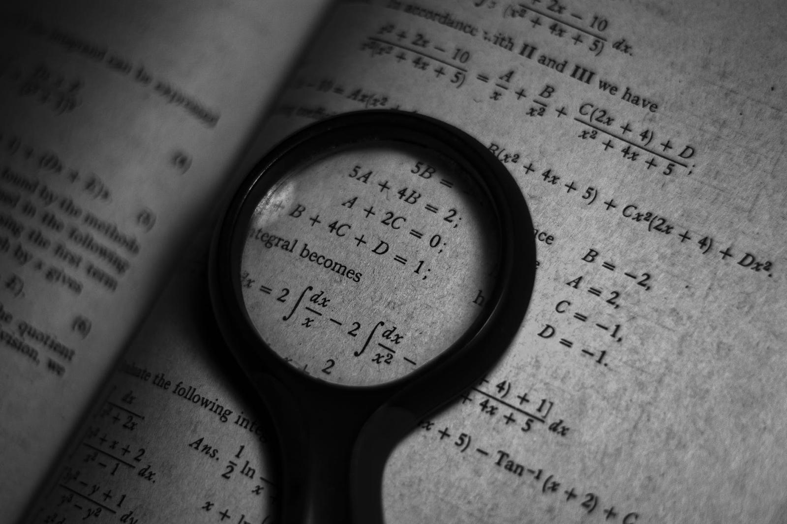 Livro de matemática com lupa colocada em cima -  Aprender programação