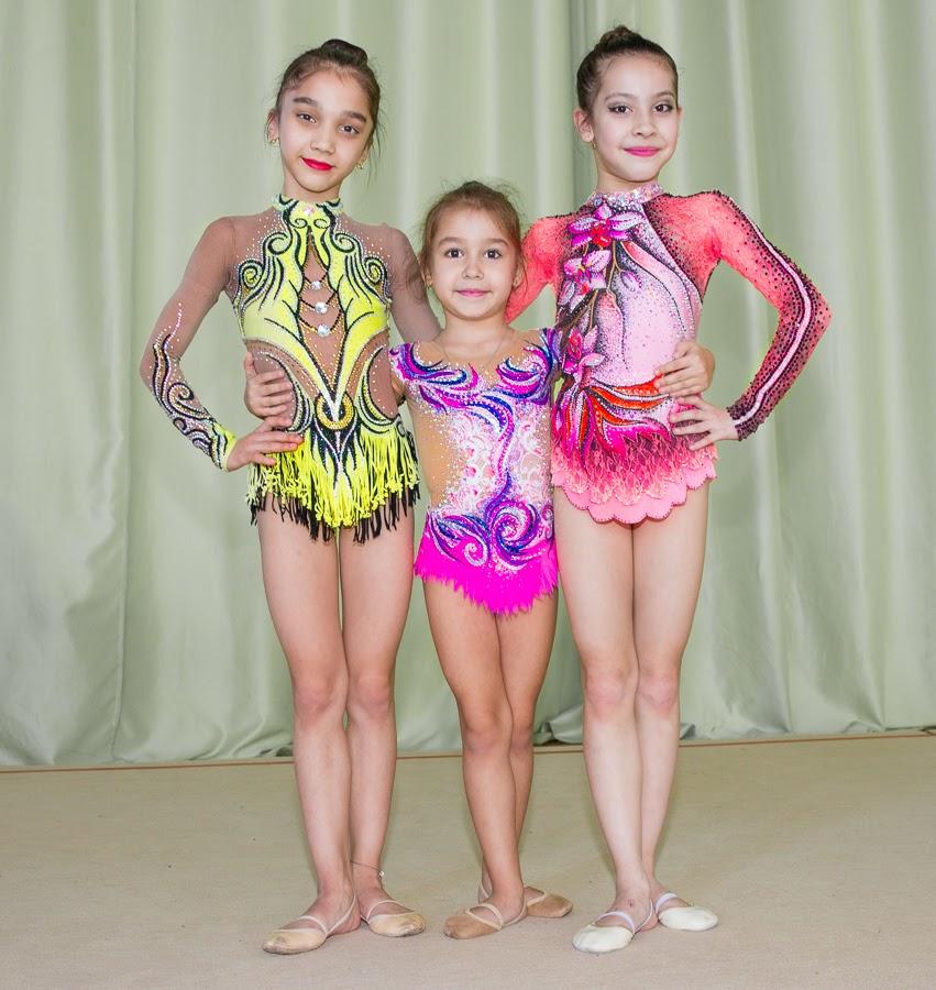 Юные девчонки гимнастки демонстрируют свои новые купальники для выступлений.