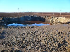 Photo: Laguna, která se nachází úplně mimo betonovou plochu na přilehlém poli cizího vlastníka oddělená pouze hliněným náspem. — Dekontaminační plocha Rokytí.