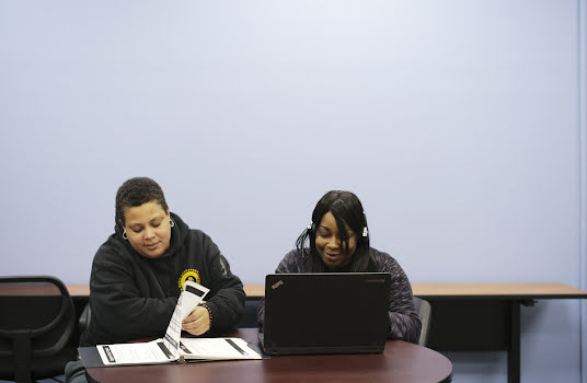 Two young people studying together with a handbook and computer.