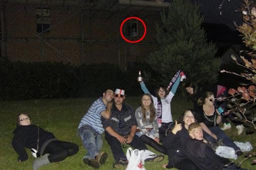 Grupo de jovenes sentados y en la ventana de un edificio a sus espaldas hay un fantasma