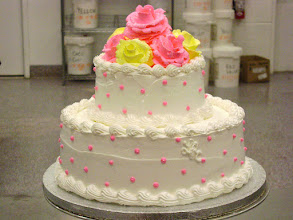 Photo: Summer Wedding Cake: 2-tiers iced in white, Italian whipped cream. Decor: single hot-pink dots, with yellow and hot-pink frosting roses adorned with edible glitter.