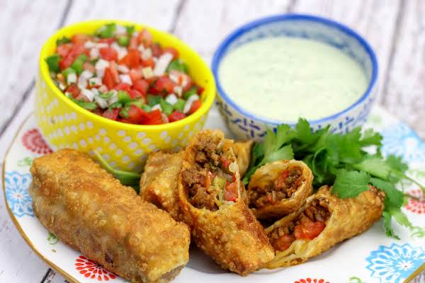 Taco Egg Rolls With Cilantro Dipping Sauce And Pico De Gallo.