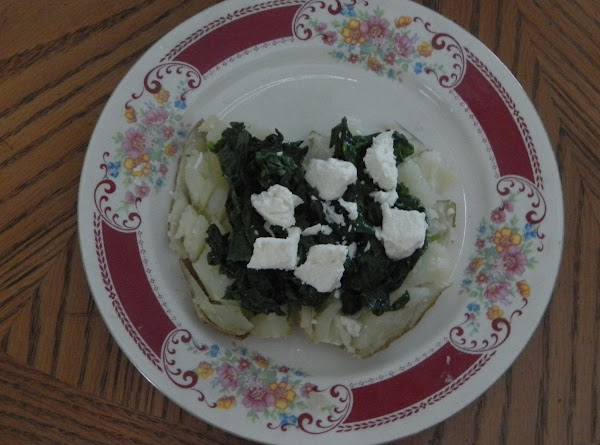 Cut the potato open, mash a little and top with the cooked spinach. Add the crumpled...