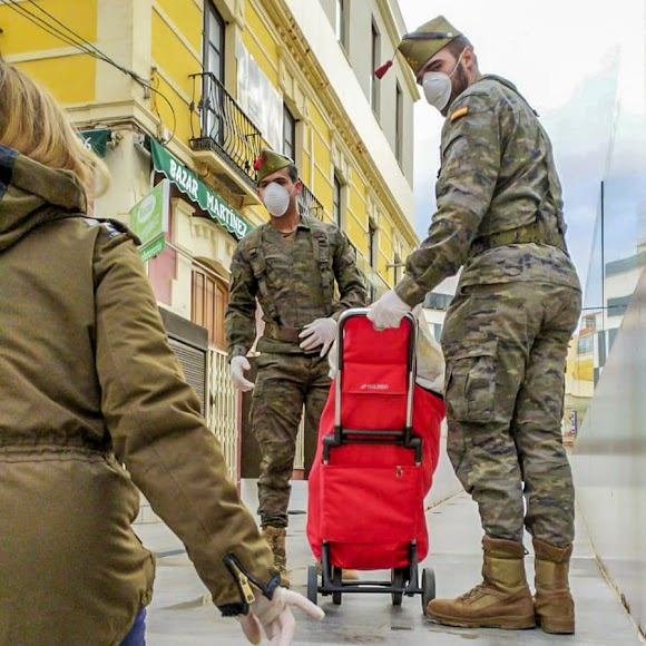 Dos legionarios ayudan en la puerta del Mercado Central.