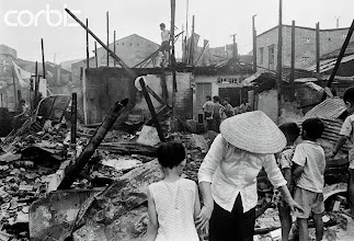 Photo: 21 Apr 1975, Saigon, South Vietnam --- The first rocket attack hit Saigon at 4:30, striking the town center and setting fire to 150 wooden houses. Fourteen died and over forty people were injured in the attacks. Inhabitants of Saigon wake up to the devastation of war. --- Image by © Jacques Pavlovsky/Sygma/CORBIS