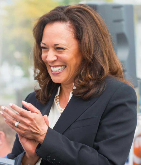 Senator Kamala Harris smiles broadly and applauds at an outdoor event.