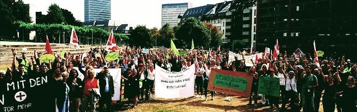 Menschenmenge auf der Wiese mit verdi-Fahnen. Transparenten z.B. «Uns fehlt Personal, wohin man schaut. Wenn sich nichts ändert, droht Burn-out!».