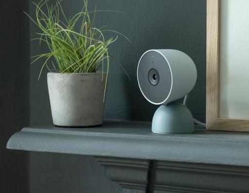 Nest Cam (wired) sits on a shelf inside a home.