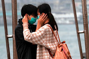 A couple wearing masks to protect them from coronavirus embrace in Hong Kong on Valentine's Day, February 14 2020.