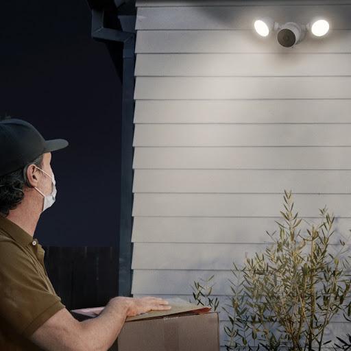 Un livreur s'approche d'une maison pour déposer un colis.