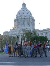 Photo: A colorguard made up of Soldiers and Airmen representing each battalion and wing that make up the Minnesota National Guard march away from the Capitol Building during Minnesota State's Sesquacentennial Celebration.