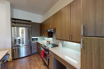 Fully-equipped kitchen with stainless steel appliances and wood-style flooring