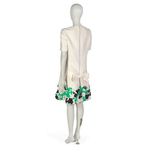 Dinner dress in white twill worsted with applied green, black and white plastic flowers at hem