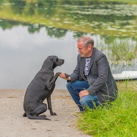 Man's best friend shake hands. by John Greene - People Portraits of Men ( big black dog, friendly dog, man and dog, portrait, man holds dogs paw, dog, john greene )