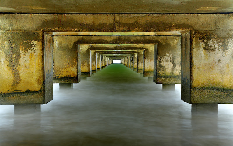 Photo: I wanted to create a surreal image that showed the interesting colors and detail under the Hanalei pier. A long exposure softened the waves which occasionally brushed up against the top part of the concrete in this image. I had to abort my 30 second planned exposure several times and run away from larger waves, until I had a good long period of smaller waves.  I like the symmetry underneath piers, so I always try to capture it if I can.
