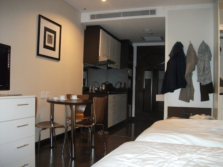 Interior of Deluxe Condotel Room: plasma TV, kitchen set, coffee table, etc.