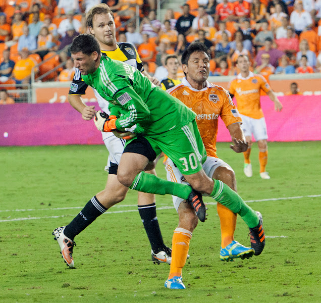 Photo: HOUSTON, TX - AUGUST 19:  Andy Gruenebaum #30 of the Columbus Crew and Brian Ching #25 of the Houston Dynamo collide during the second half at BBVA Compass Stadium on August 19, 2012 in Houston, Texas.  (Photo by Bob Levey/Getty Images)