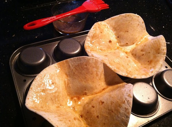 PREHEAT OVEN TO 350.  PLACE TORTILLAS ON THE BOTTOM OF A MUFFIN TIN...